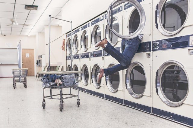 woman with up half of her body inside laundry machine