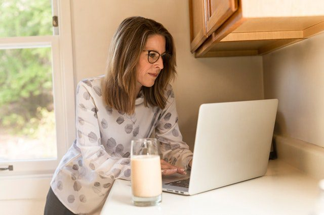 Woman looking at laptop inside her home