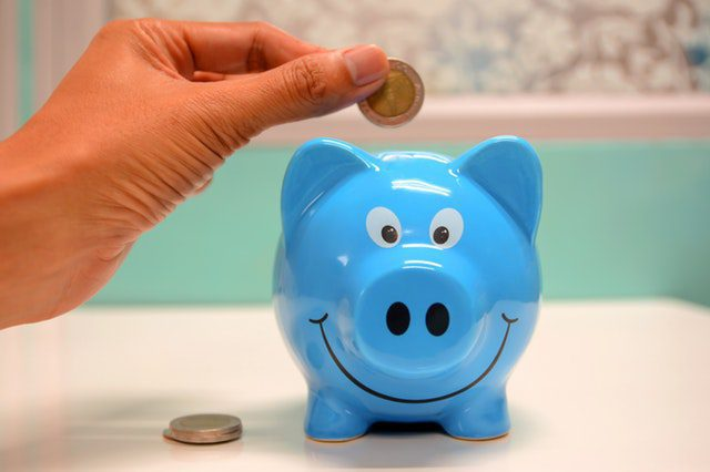 Saving money in a blue piggy bank