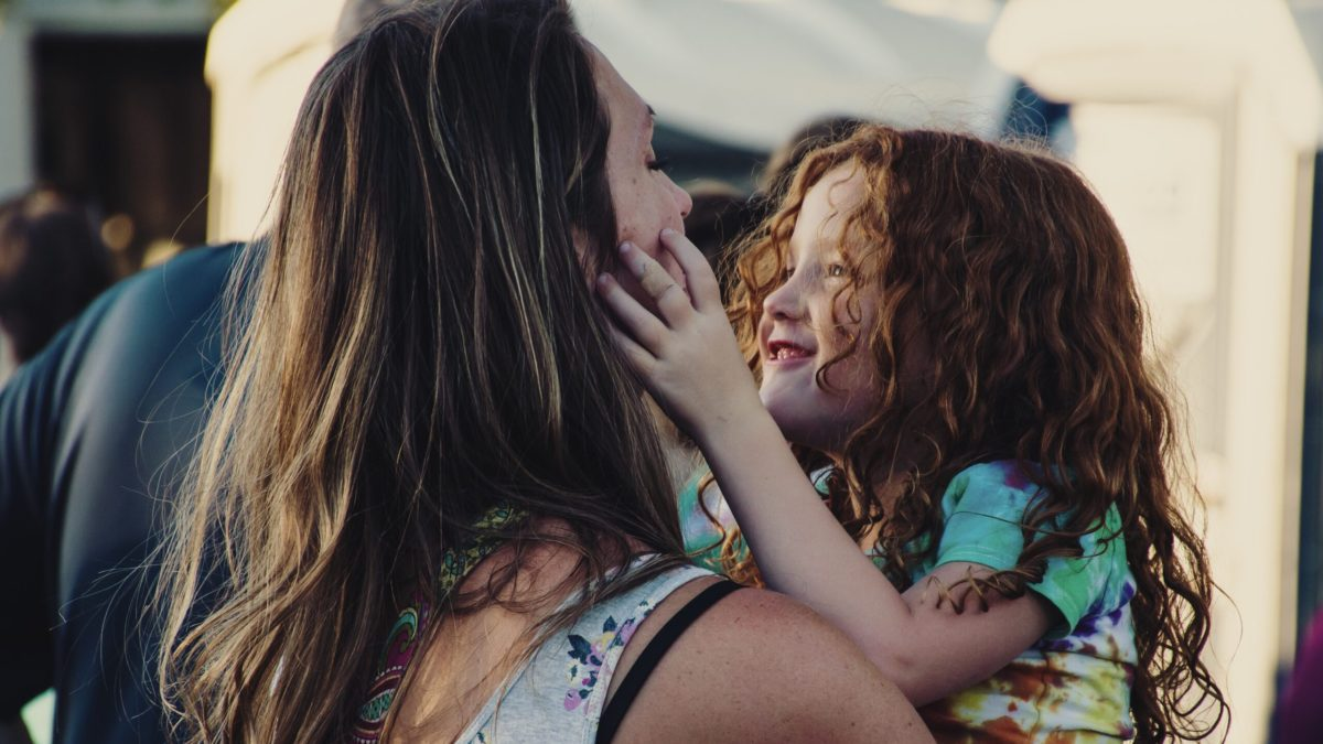 Mother holding daughter with red hair who is smiling and squeezing her mother's face.